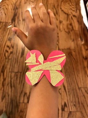 Making a Kid's Paper Butterfly Bracelet - child wearing the red butterfly
