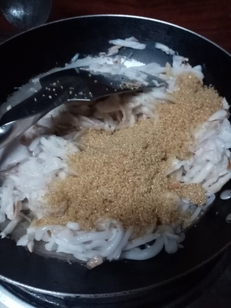 sugar added to coconut meat in pan