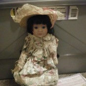 Identifying a Porcelain Doll - doll wearing a floral dress and straw hat