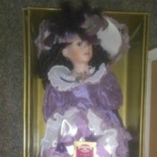 Value of a Collectible Memories Porcelain Doll - doll in box wearing a satin dress with purple ribbon trim
