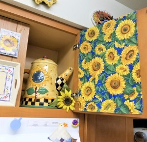 Above the Stove Sunflower Collection - view of one side of cabinet and fabric draped door and coffee pot