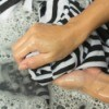 Hand washing a black and white striped shirt.