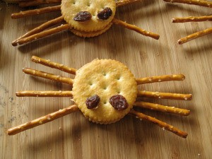 Spider Halloween cracker made with Ritz crackers, pretzels for the legs and raisins for the eyes.