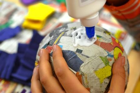 Putting glue on paper mache ball.