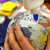 Putting glue on paper mache ball.