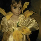 Identifying Porcelain Dolls - doll wearing a satin dress with yellow lily petals