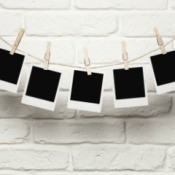 Polaroid photos pinned to a string hanging on a wall.