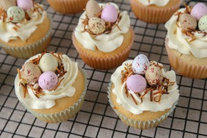 Cupcakes decorated with colorful candy eggs and toasted coconut.