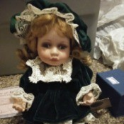 Value of a Collectible Memories Doll - small doll wearing a dark green velvet dress with lace trim