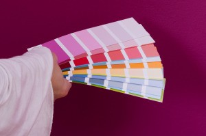 Hand holding up a stack of paint samples to a magenta wall.