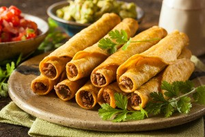 Taquitos stacked on a plate.