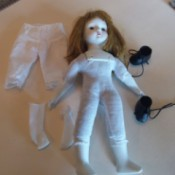 Identifying a Porcelain Musical Doll -  doll with white porcelain head, hands, and feet.