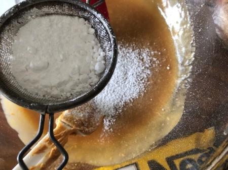 sifting powdered sugar into bowl