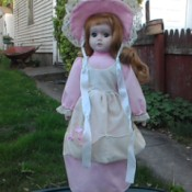 Identifying a Heritage Porcelain Doll - doll wearing a long pink dress with white apron and matching hat