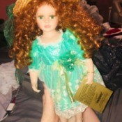 Value of a Seymour Mann Limited Edition Doll - doll wearing a straw hat and green floral dress