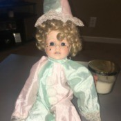 Identifying a Porcelain Doll - doll wearing a pastel pink and green outfit and hat