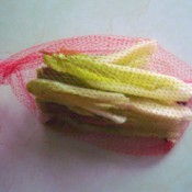 Lettuce leaves in a mesh produce bag.