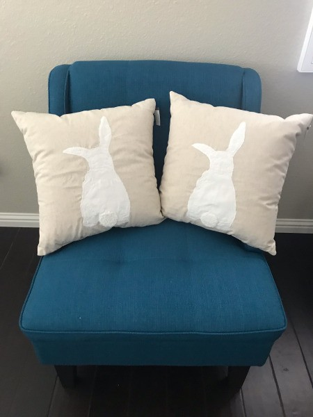 Two rabbit pillows on a blue chair.