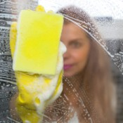 A woman washing a window with lots of soapy streaks.