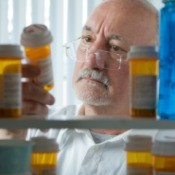 A man looking through a medicine cabinet for his prescription.