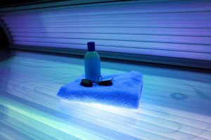 A tanning bed with a towel and other supplies.