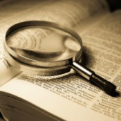 An open dictionary with a magnifying glass.