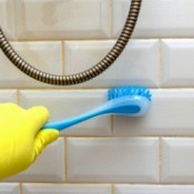 Cleaning mold from a tiled wall in a bathroom.