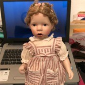 Identifying a Danbury Mint Porcelain Doll - doll with braids pinned up, wearing a striped pinafore dress
