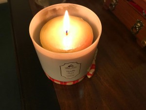A burning candle that has been replaced in the candle holder.