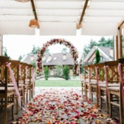 Wedding venue with wooden chairs, flower petal path leading to a flower arch.