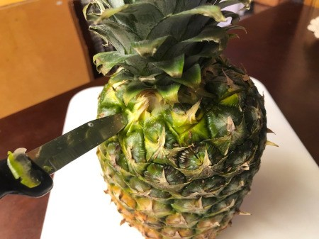 cutting top of pineapple diagnolly with knife