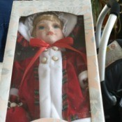 Value of Leonardo Collection Porcelain Dolls - doll wearing a red coat trimmed in white - still in box