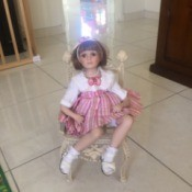 Identifying a Porcelain Doll - doll sitting on a wicker style chair
