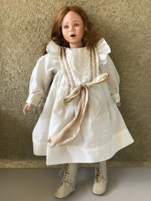 Identifying a Porcelain Doll - doll wearing period dress and high top shoes, has pink eyes