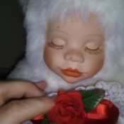 Value of Classical Treasures Porcelain Dolls - doll wearing a white fur suit with a red heart on the front