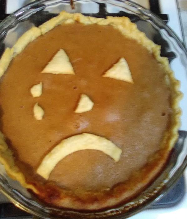 A pumpkin pie with a sad face.