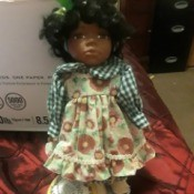 Value of a Crowne Porcelain Doll - African American doll wearing a floral pinafore dress with a checkered blouse