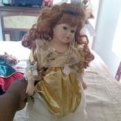 Value of Seymour Mann Dolls - doll wearing a long dress with a gold overshirt