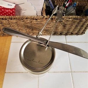 How to Reuse Your Canning Jar Lids for Crafts - butter knife on edge of canning jar lid and lid opener end of can opener in place
