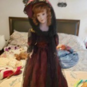 Identifying a Porcelain Doll - doll wearing a long dark red dress with hat and black lace veil