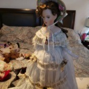 Identifying a Porcelain Doll - doll wearing a hat and gold trimmed fancy long white dress with lace around the hem