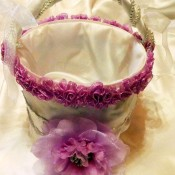 Homemade Recycled Flower Girl Basket - white fabric covered bucket with purple-red flowers around the top and a large flower on the front