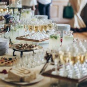 Stylish champagne glasses and food appetizers on table.