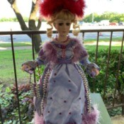 Identifying a Porcelain Doll - doll wearing a feather hat and long dress