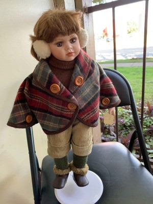 Value of a Show Stoppers Porcelain Doll - doll wearing ear muffs and a plaid cape/coat