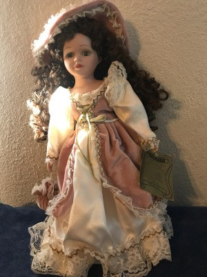 Value of a Seymour Mann Connoisseur Collection Doll - doll wearing a long ivory dress with a rose over skirt and hat