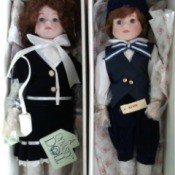 Value of a Pair of Dynasty Porcelain Dolls - dolls in boxed wearing navy and black clothing over white shirt or blouse