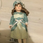 Identifying a Vintage Porcelain Doll - doll wearing a print dress and matching cap