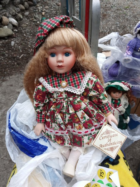 Selling Porcelain Dolls - doll wearing a print dress and matching green and red plaid hat