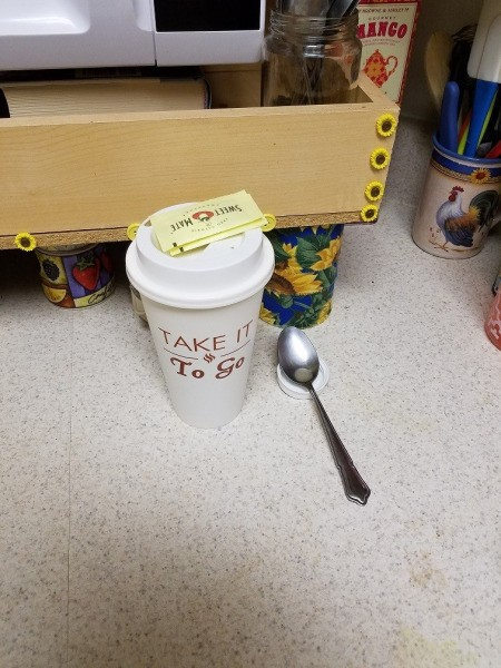 A plastic lid being used as a small spoon rest for coffee.